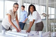 Stock Photo of Smiling architects analyzing plans together