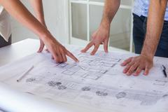Architects working on blueprints together Stock Photos