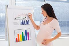 Attractive pregnant businesswoman drawing graph at work Stock Photos