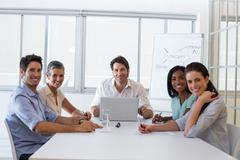 Attractive business people smiling at the camera - stock photo