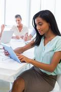 Attractive businesswoman using tablet with coworkers behind - stock photo