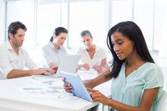 Stock Photo of Attractive businesswoman using tablet with coworkers behind
