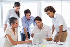 Stock Photo of Business people interacting and looking at laptop