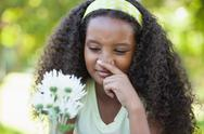 Stock Photo of Young girl holding a flower and covering her nose in the park