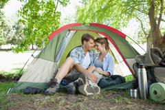 Stock Photo of Cute couple sitting in their tent showing affection