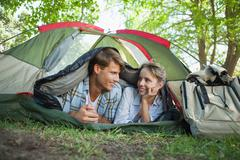 Stock Photo of Cute couple lying in their tent smiling at each other
