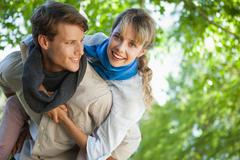 Stock Photo of Cute woman smiling at camera in the park while getting a piggy back