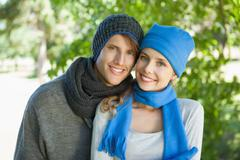 Cute couple smiling at camera in hats and scarves - stock photo