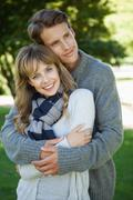Stock Photo of Cute couple hugging with girl smiling at camera in the park