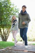 Cute couple walking hand in hand in the park - stock photo