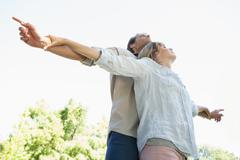 Carefree couple standing with arms out in the park - stock photo