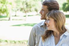 Carefree couple standing in the park and smiling - stock photo