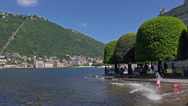 Stock Video Footage of Italy, lake Como, children playiong on embankment.