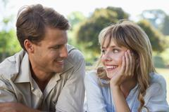 Carefree couple lying in the park smiling at each other - stock photo