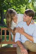 Stock Photo of Affectionate couple relaxing on park bench together