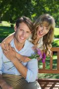 Cute couple smiling at camera in the park with girl holding flowers - stock photo