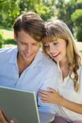 Stock Photo of Cute couple sitting on park bench together looking at laptop