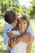Cute couple hugging in the park with girl smiling at camera - stock photo