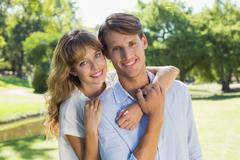 Cute couple smiling at camera together in the park - stock photo