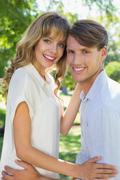 Cute couple hugging and smiling at camera in the park - stock photo