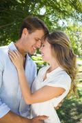 Stock Photo of Cute couple hugging in the park and smiling at each other