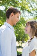 Stock Photo of Attractive couple smiling at each other in the park