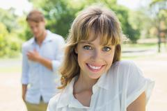 Stock Photo of Beautiful blonde smiling at camera with boyfriend in background