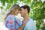 Stock Photo of Cute couple smiling and hugging in the park