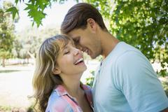 Stock Photo of Cute couple laughing and hugging in the park