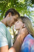 Cute smiling couple hugging in the park - stock photo