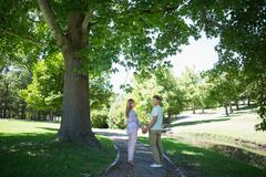 Stock Photo of Cute affectionate couple walking hand in hand in the park