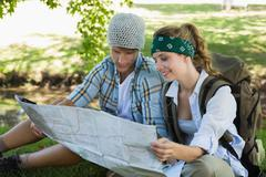 Active couple sitting down on a hike reading map Stock Photos
