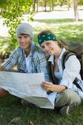 Stock Photo of Active smiling couple sitting down on a hike holding map