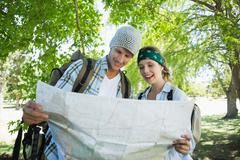 Active smiling couple on a hike consulting the map Stock Photos