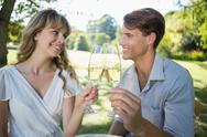Stock Photo of Cute couple sitting outside toasting with champagne