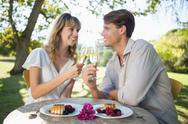 Stock Photo of Cute happy couple sitting outside toasting with champagne with dessert