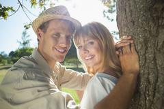 Cute couple leaning against tree in the park smiling at camera Stock Photos