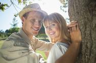 Stock Photo of Cute couple leaning against tree in the park smiling at camera