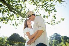 Cute couple standing in the park embracing - stock photo