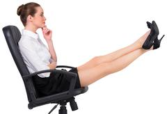 Stock Photo of Businesswoman sitting on swivel chair with feet up