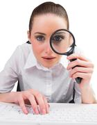 Stock Photo of Businesswoman typing and looking through magnifying glass