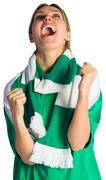 Cheering football fan in green jersey - stock photo