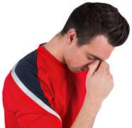 Disappointed football fan looking down - stock photo
