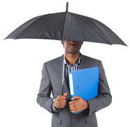 Stock Photo of Businessman standing under umbrella