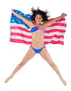 American girl in bikini leaping holding flag Stock Photos