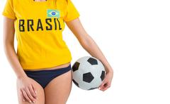 Fit girl in bikini and brasil tshirt holding ball - stock photo