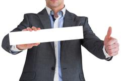 Businessman in grey suit showing card - stock photo
