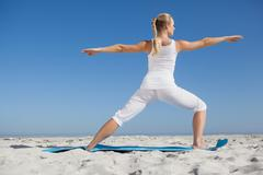 Stock Photo of Calm woman standing in warrior pose on beach