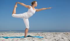 Stock Photo of Blonde woman standing in warrior pose on beach