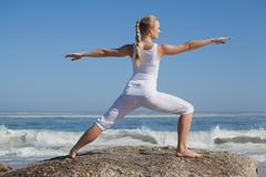 Stock Photo of Blonde woman standing in warrior pose on beach on rock